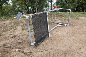 The single fog collector (SFC) can be seen here temporarily placed on its side to enable access to the top frame bar.  The solar panel is mounted at the top of the unit.